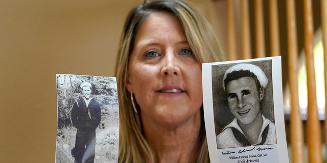 Teri Mann Whyatt displays photos of her uncle, William Edward Mann, who died on the USS Arizona during the bombing of Pearl Harbor, at her home Wednesday, July 14, 2021, in Newcastle, Wash. (AP Photo/Elaine Thompson)