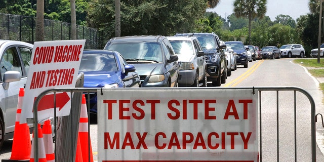 Signage stands at the ready, foreground, in case COVID-19 testing at Barnett Park reaches capacity, as cars wait in line in Orlando, Florida, Thursday, July 29, 2021. (Associated Press)