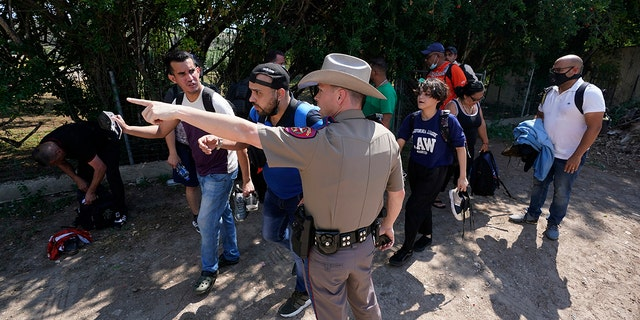 A Texas Department of Public Safety officer in Del Rio, Texas directs a group of migrants who crossed the border and turned themselves in on June 16, 2021. . (Associated Press)