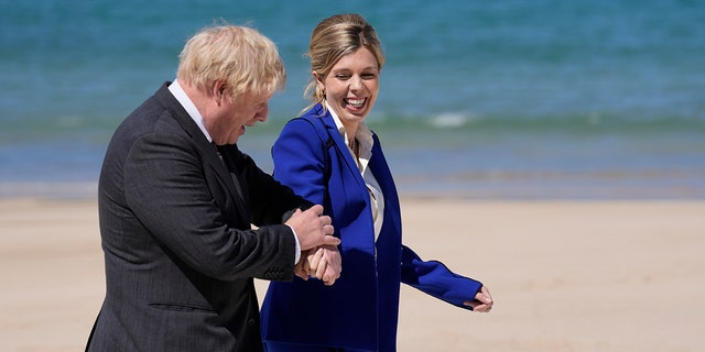 British Prime Minister Boris Johnson and his wife Carrie walk on the boardwalk during the G7 meeting in St. Ives, England, June 12, 2021. (Associated Press)