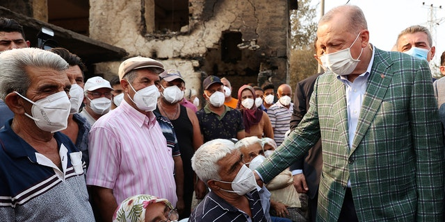 Turkey's President Recep Tayyip Erdogan speaks with villagers in front of a wildfire-destroyed house in Manavgat, Antalya, Turkey, Saturday, July 31, 2021. The death toll from wildfires raging in Turkey's Mediterranean towns rose to six Saturday after two forest workers were killed, the country's health minister said. Fires across Turkey since Wednesday burned down forests, encroaching on villages and tourist destinations and forcing people to evacuate.