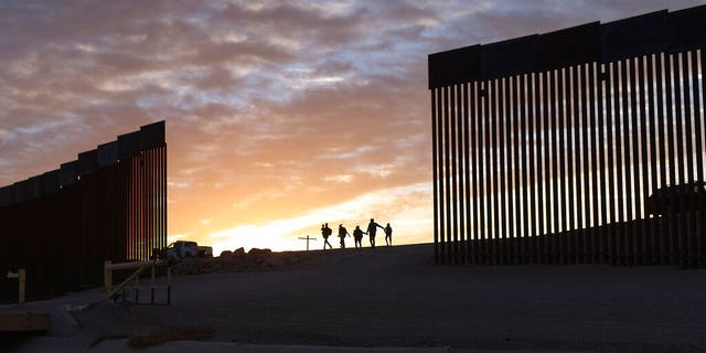 June 10, 2021: A pair of migrant families from Brazil pass through a gap in the border wall to reach the United States.