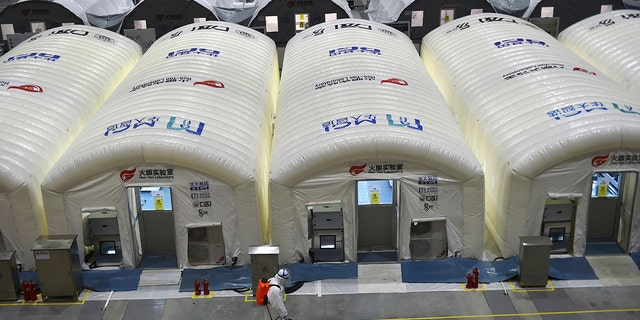 A worker disinfects the flooring outside the inflated cabins at the pop-up Huo-Yan Laboratory set up in an expo center to test samples for covid-19 virus in Nanjing in east China's Jiangsu province Wednesday, July 28, 2021.