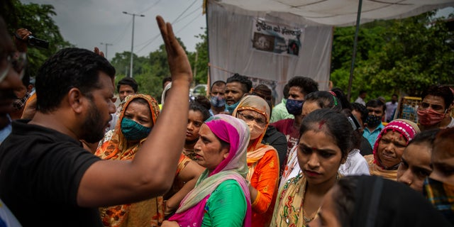 A man tries to calm protesters down as they try to block a street outside a crematorium where a 9-year-old girl from the lowest rung of India's caste system was, according to her parents and protesters, raped and killed earlier this week, in New Delhi, India, Thursday, Aug. 5, 2021. (AP Photo/Altaf Qadri)
