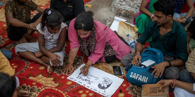 Tina Verma, 27, a social activist, makes a placard at a demonstration site outside a crematorium where a 9-year-old girl from the lowest rung of India's caste system was, according to her parents and protesters, raped and killed earlier this week, in New Delhi, India, Thursday, Aug. 5, 2021. (AP Photo/Altaf Qadri)