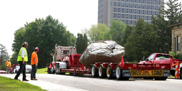 A flatbed trailer pull away from Observatory Hill with Chamberlin Rock in tow in Madison, Wis., Friday, Aug. 6, 2021. The University of Wisconsin is removing the 70-ton boulder from its Madison campus at the request of minority students who view the rock as a symbol of racism. Chamberlin Rock, on the top of Observatory Hill, is named after Thomas Crowder Chamberlin, a geologist and former university president.   (Kayla Wolf/Wisconsin State Journal via AP)
