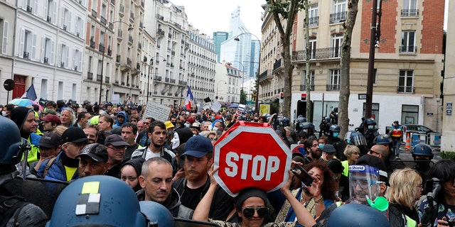 Anti-vax protesters gather to protest against the vaccine and vaccine passports, during a demonstration in Paris, France, Saturday Aug. 7, 2021.