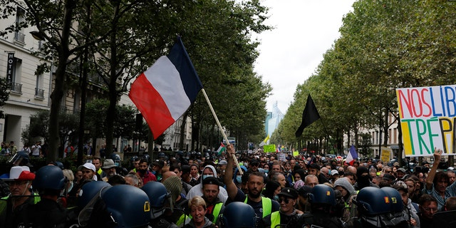 Anti-vax protesters face police during a protest against the vaccine and vaccine passports, in Paris, France, Saturday Aug. 7, 2021.