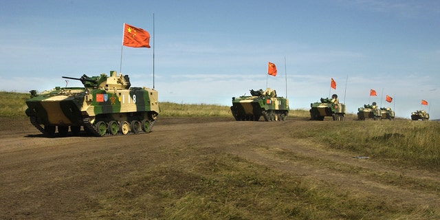 FILE - In this Aug. 13, 2007, file photo, a convoy of Chinese APCs roll by during a rehearsal for a massive joint military exercise by the two former Cold War rivals, the first on Russia's territory in the Chelyabinsk region in Russia's Ural Mountains.