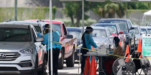 People wait in cars to get a COVID-19 test, Wednesday, Aug. 11, 2021, in Miami. COVID-19 has strained some Florida hospitals so much that ambulance services and fire departments can no longer respond as usual to every call. (AP Photo/Marta Lavandier)