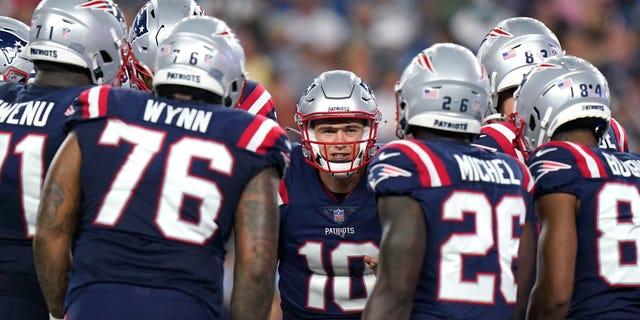 Quarterback New England Patriots Mac Jones, tengah, berkumpul dengan rekan satu tim selama paruh pertama pertandingan sepak bola NFL pramusim melawan Tim Sepak Bola Washington, Kamis, 12 Agustus 2021, di Foxborough, Mass. (AP Photo/Steven Senne)