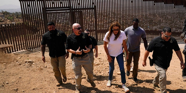 Caitlyn Jenner, center in white shirt, a Republican candidate for California governor, walks alongside members of the National Border Patrol Council during a visit to the border Friday, Aug. 13, 2021, in San Diego. (Associated Press)