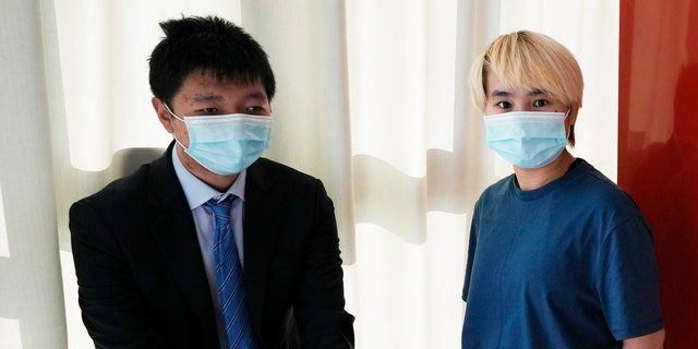 """Wu Huan, right, and Wang Jingyu stand together in a safe house in the Ukraine on Wednesday, June 30, 2021. Wu claims that she was held for eight days at a Chinese-run """"black site"""" in Dubai along with at least two Uyghurs, in what may be the first evidence that China is operating a secret detention facility beyond its borders. She was on the run from the threat of being sent back to her home country because of her support of her fiance, Wang, a perceived Chinese dissident. (AP Photo)"""