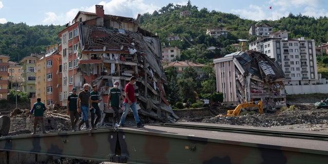 Cilvēki staigā pa pagaidu tiltu, ko militāristi uzcēla Bozkurtas pilsētā Turcijas Kastamonu provincē svētdien, 2021. gada 15. augustā, pēc plūdiem.  Turcija ir nosūtījusi kuģus, lai palīdzētu evakuēt cilvēkus un transportlīdzekļus no plūdos skartās Melnās jūras ziemeļu pilsētas, jo svētdien notikušās katastrofas upuru skaits pieauga līdz vismaz 62 un daudzi citi joprojām ir pazuduši.  (AP fotoattēls)