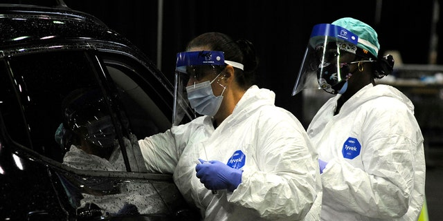 Workers from USA Health test a person for COVID-19 during a drive-up clinic in Mobile, Alabama, Aug. 12, 2021. (Associated Press)