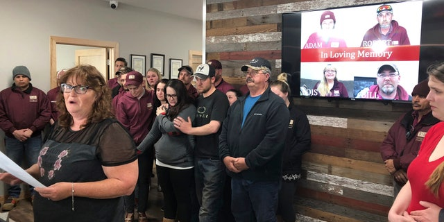 In this Friday, April 5, 2019, file photo, Jackie Fakler, co-owner of RJR Maintenance and Management, is surrounded by employees, in Mandan, North Dakota, as she reads a statement about the slayings of four RJR employees earlier in the week. (AP Photo/James MacPherson, File)