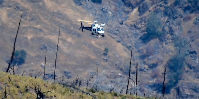 A helicopter hovers over a remote area northeast of the town of Mariposa, Calif., on Wednesday, Aug. 18, 2021. (Craig Kohlruss/The Fresno Bee via AP)