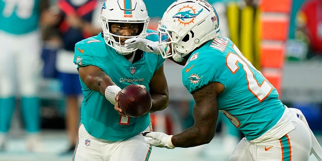 Miami Dolphins quarterback Tua Tagovailoa (1) hands the ball to running back Salvon Ahmed (26) during the first half of a preseason NFL football game against the Atlanta Falcons, Saturday, Aug. 21, 2021, in Miami Gardens, Fla. (AP Photo/Lynne Sladky)