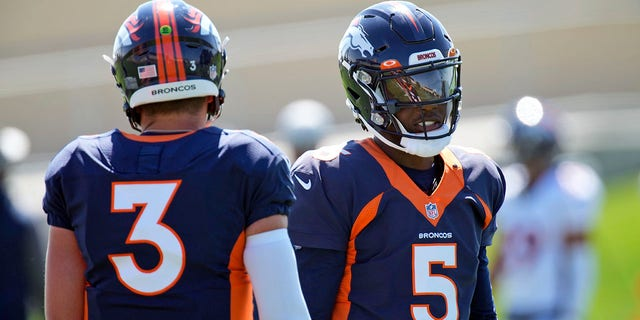 Denver Broncos quarterbacks Teddy Bridgewater, right, and Drew Lock take part in drills during NFL football practice at the team's headquarters Wednesday, Aug. 25, 2021, in Englewood, Colo.