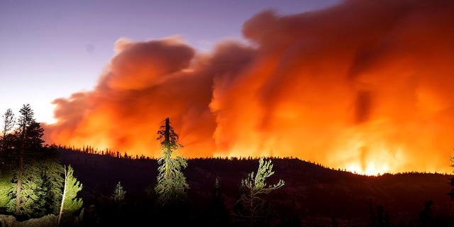 Seen in a long camera exposure, the Caldor Fire burns on Sunday, Aug. 29, 2021, in Eldorado National Forest, Calif. (AP Photo/Noah Berger)