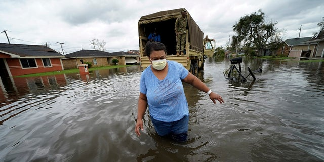 Jerilyn Collins wades through floodwaters Monday after being transported by the Louisiana National Guard back to her home to retrieve medicine for herself and her father, after she evacuated from rising water in the aftermath of Hurricane Ida in LaPlace, La.
