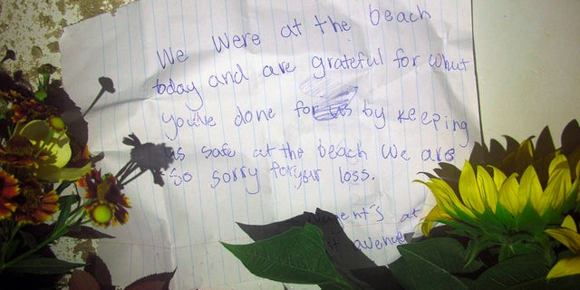 A bouquet of flowers appears to have been placed in a lifeguard's chair on the sand at a beach in Berkeley Township, NJ, where a young lifeguard was killed and seven others were injured on Monday, August 30, 2021.  (AP Photo / Wayne Parry)