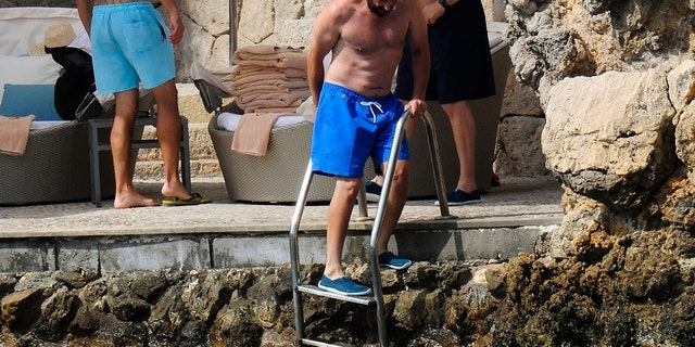 Adam Sandler mixes a little business and pleasure as he takes a break from his filming duties on the beach in Palma De Mallorca.