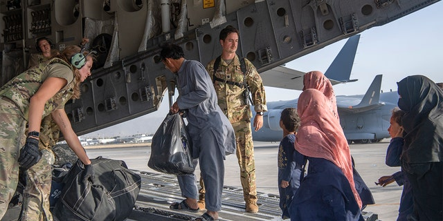 In this image provided by the U.S. Air Force, U.S. Air Force loadmasters and pilots assigned to the 816th Expeditionary Airlift Squadron, load people being evacuated from Afghanistan onto a U.S. Air Force C-17 Globemaster III at Hamid Karzai International Airport in Kabul, Afghanistan, Tuesday, Aug. 24, 2021.
