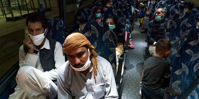 Families evacuated from Kabul, Afghanistan, sit on a bus after they arrived at Washington Dulles International Airport in Chantilly, Va., Sabato, Ago. 21, 2021.