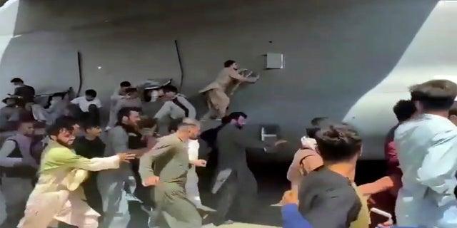 Hàng trăm người chạy cùng chiếc máy bay vận tải C-17 của Không quân Mỹ, một số người đã lên máy bay khi nó di chuyển dọc theo đường băng của sân bay quốc tế, ở Kabul, Afghanistan, hôm thứ Hai.