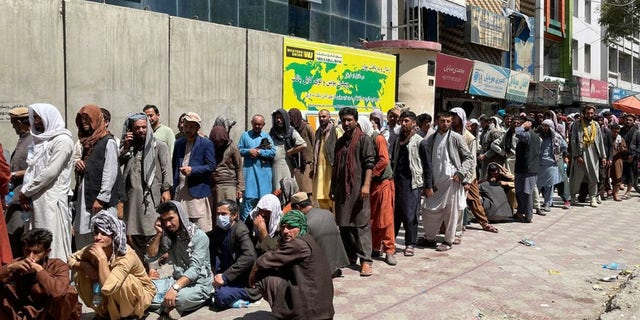 Afghans line up outside a bank to take out cash as people keep waiting at Hamid Karzai International Airport to leave the country after Taliban's takeover in Kabul, Afghanistan, on August 25, 2021.