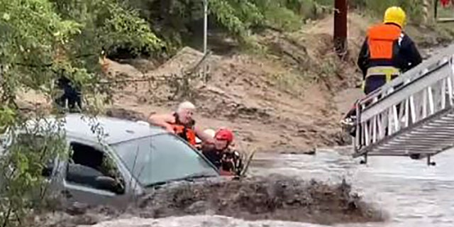 Rescuers pulled a woman to safety after she became trapped inside a vehicle amid a flash flood near Tucson, Ariz., on Tuesday.