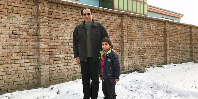 This photo provided by Bahaudin Mujtaba shows Noman Mujtaba, left, and Bahaudin Mujtaba in Kabul, Afghanistan, on Dec. 21, 2017. The boy, now 10 years old, is a distant relative of Mujtaba. (Courtesy of Bahaudin Mujtaba via AP)