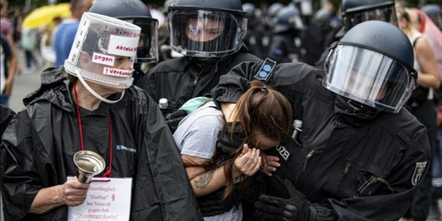 Police arrest a demonstrator at an unannounced demonstration at the Victory Column, in Berlin, Sunday Aug. 1, 2021, during a protest against coronavirus restrictions. (Fabian Sommer/dpa via AP)