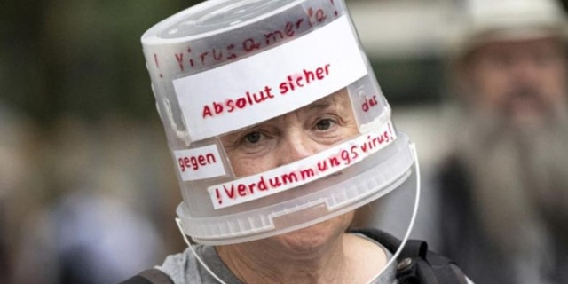 A demonstrator walks through Berlin-Charlottenburg with a plastic bucket placed on his head reading 'Absolutely safe against the stupidity virus', in Berlin, Sunday Aug. 1, 2021, during a protest against coronavirus restrictions. (Fabian Sommer/dpa via AP)