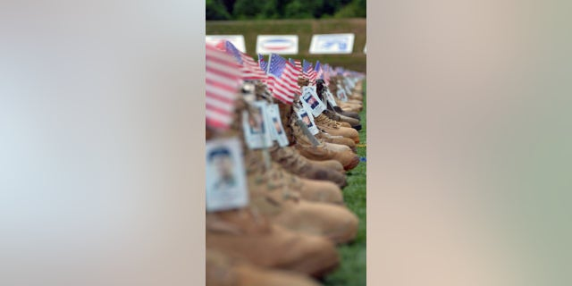 To set up the memorial boot display, volunteers carefully tie each lace and place an empty water bottle inside each boot to keep it erect.