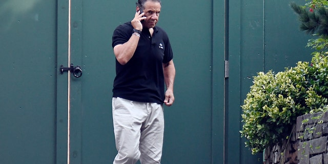 Governor Andrew Cuomo talks on the phone while walking with his dog Captain at the New York State Executive Mansion on Saturday, August 7, 2021, in Albany, NY