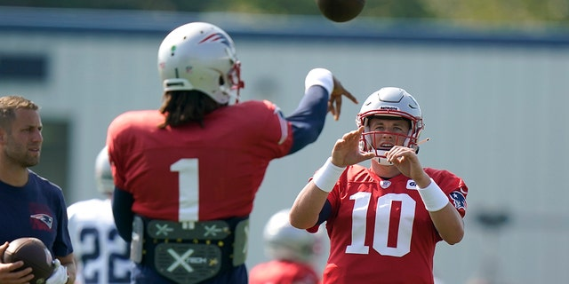 New England Patriots quarterback Cam Newton (1) passes the ball to Patriots quarterback Mac Jones (10) during a joint NFL football practice with the New York Giants, Thursday, Aug. 26, 2021, in Foxborough, Mass. (AP Photo/Steven Senne)
