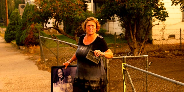 Rose Mooney carries photos from her home, which is under an evacuation warning, as the Dixie Fire burns towards Susanville, Calif., on Monday, Aug. 16, 2021.