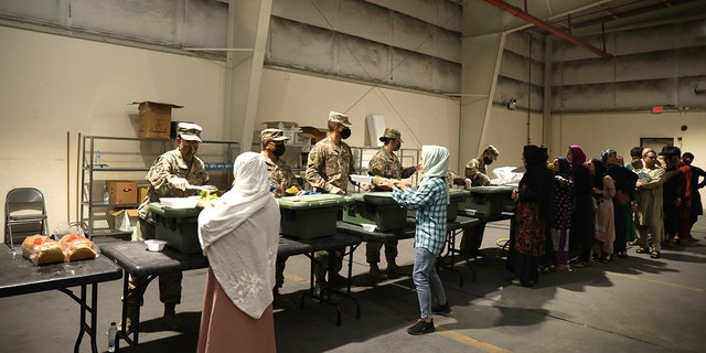 US Army soldiers serve lunch to Afghan civilians while they complete Special Immigrant Applications.