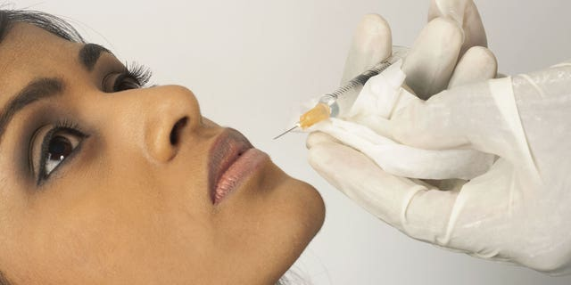 Doctor injecting collagen into young womans lip