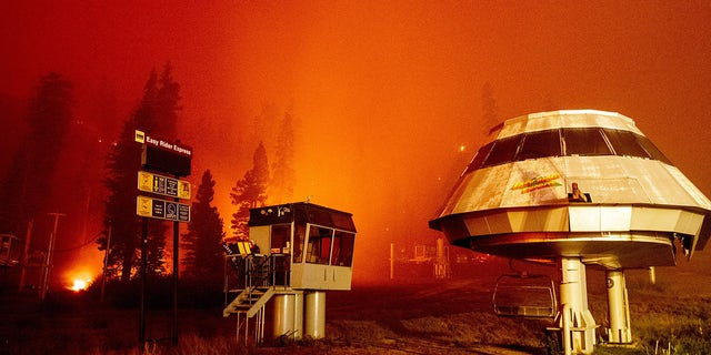 Flames surround a chair lift at Sierra-at-Tahoe Resort, a skiing area, during the Caldor fire in Twin Bridges, California on August 30, 2021. (Photo by JOSH EDELSON / AFP) (Photo by JOSH EDELSON/AFP via Getty Images)