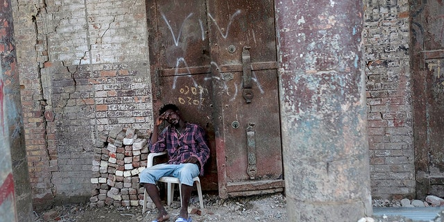 A man sits in front of a damaged building in Jeremie, Haiti, Wednesday, Aug. 18, 2021, four days after the city was struck by a 7.2-magnitude earthquake. (AP Photo/Matias Delacroix)