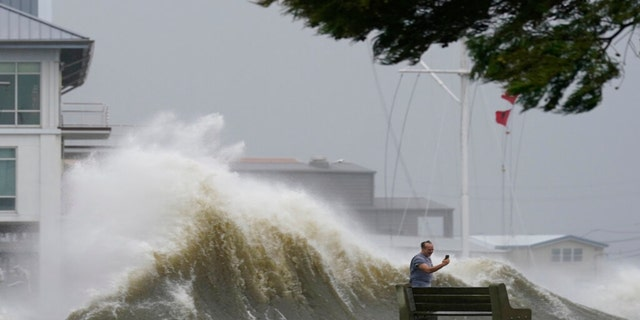 A man takes pictures of high waves along the shore of Lake Pontchartrain as Hurricane Ida nears, Sunday, Aug. 29, 2021, in New Orleans.