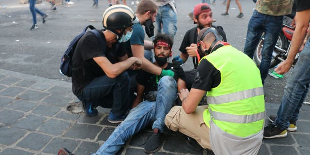 Protesters tend to a man injured during demonstrations on the anniversary of a massive explosion in Beirut.