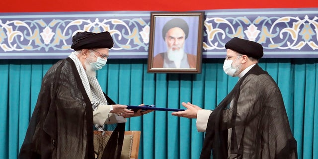 Iran Supreme Leader Ayatollah Ali Khamenei, left, gives his official seal of approval to newly elected President Ebrahim Raisi in an endorsement ceremony in Tehran, Iran, on Tuesday. A portrait of the late revolutionary founder Ayatollah Khomeini hangs in the background. (Office of the Iranian Supreme Leader/AP)