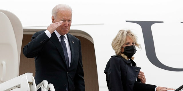 President Joe Biden salutes as first lady Jill Biden looks on from the stairs of Air Force One before boarding at Andrews Air Force Base, Md., for a trip to Dover Air Force Base, Del., Sunday, Aug. 29, 2021. (AP Photo/Luis M. Alvarez)