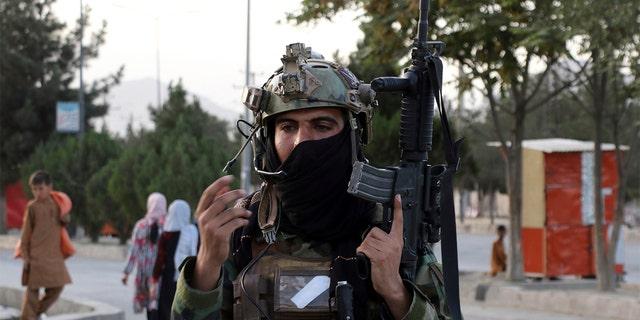 तालिबान लड़ाके अफगानिस्तान के काबुल में हामिद करजई अंतरराष्ट्रीय हवाई अड्डे के गेट के पास एक चौकी पर पहरा देते हैं, शनिवार, अगस्त २८, २०२१