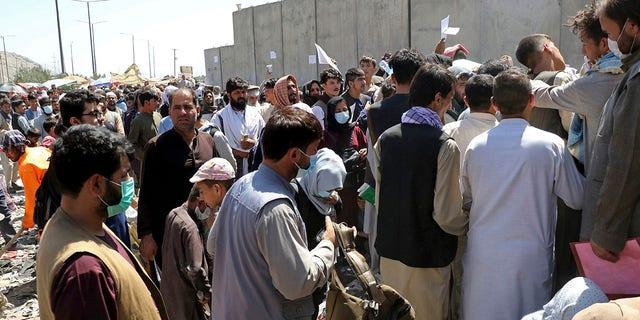 数百人, some holding documents, gather near an evacuation control checkpoint on the perimeter of the Hamid Karzai International Airport, 在喀布尔, 阿富汗, 星期四, 八月. 26, 2021.