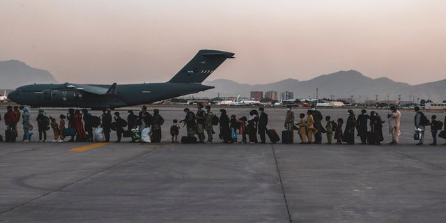 In this image provided by the U.S. Marine Corps, evacuees wait to board a Boeing C-17 Globemaster III, at Hamid Karzai International Airport, 受け入れ, アフガニスタン, 月曜日に. (AP/Sgt. Isaiah Campbell/U.S. Marine Corps)